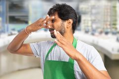 Employee at fish market making bad smell gesture. Indian male employee at fish market or supermarket making bad smell gesture and disgusted expression as holding royalty free stock images