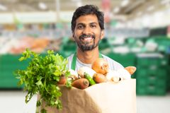 Grocery store employee holding bag of vegetables. Indian male grocery store or hypermarket employee holding brown paper bag of vegetables with friendly smile stock photography