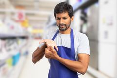 Hypermarket employee stretching fingers. Indian male hypermarket or supermarket employee stretching fingers as getting ready for physical effort with hurting royalty free stock photography
