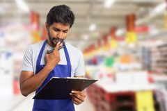 Hypermarket employee thinking with clipboard in hand. Indian male hypermarket or supermarket employee thinking as fingers touching chin with clipboard and market stock photo