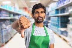 Hypermarket employee showing dislike gesture. Indian male hypermarket or supermarket employee wearing green apron showing dislike gesture with thumb finger down royalty free stock image
