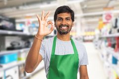 Person working at hypermarket showing okay gesture. Indian male person working at hypermarket or supermarket showing okay gesture with fingers and friendly smile royalty free stock photography