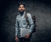 The Indian male student holds laptop and backpack. The Indian male student holds laptop and backpack over grey studio background Stock Photos