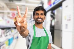 Supermarket employee showing victory gesture. Indian male supermarket employee wearing green apron showing victory or peace gesture as celebrating success stock photography
