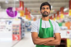 Supermarket employee portrait with crossed arms. Indian male supermarket or hypermarket employee portrait picture wearing green apron with crossed arms and stock photo