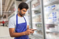 Supermarket employee texting on phone. Indian male supermarket or hypermarket employee texting on phone with focused expression wearing eyeglasses and blue apron royalty free stock photos