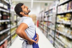 Supermarket worker with backache holding painful area. Indian male supermarket or hypermarket worker with hurting expression because of backache holding hands on stock photography
