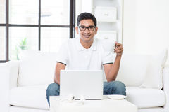 Indian male using computer at home. Stock Photos