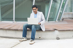 Indian male using laptop. Outdoor Royalty Free Stock Images