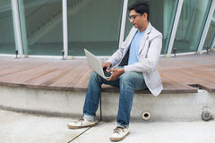 Indian male using laptop. Outdoor Stock Image