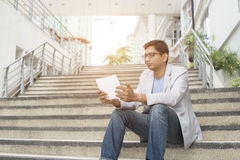 Indian male. Using tablet outdoor Stock Photo