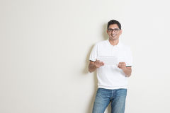 Indian male using tablet. Portrait of handsome Indian guy using tablet pc, standing on plain background with shadow, copy space at side Royalty Free Stock Photo