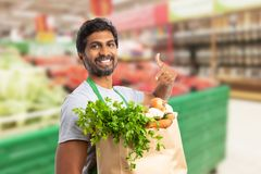 Worker at grocery store holding vegetable bag. Indian male worker at grocery store or supermarket smiling as holding vegetable bag and pointing at it with index stock photo