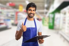 Worker at hypermarket showing thumb-up holding clipboard. Indian male worker at hypermarket or supermarket showing thumb-up like gesture while holding clipboard royalty free stock image