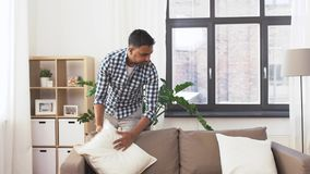 Indian man arranging sofa cushions at home stock video footage