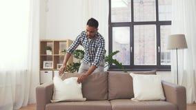Indian man arranging sofa cushions at home stock video
