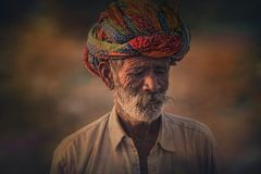 Old Rajasthani man against the background of his camels. Indian man attended the annual Pushkar Camel Mela Royalty Free Stock Photo