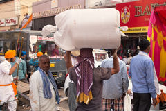 Indian man carrying bundle on his head in Chandni Chowk street, Royalty Free Stock Images