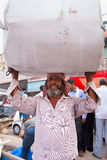Indian man carrying bundle on his head in Chandni Chowk street, Royalty Free Stock Photo
