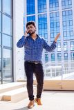 Indian man in casual cloth with beard calling in front of an office building. stock photography