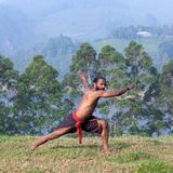 Indian man doing yoga exercises on green grass. Indian man doing yoga exercise on green grass in Kerala, South India Royalty Free Stock Photography