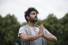 Indian man doing yoga exercise in a park Stock Photography