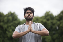 Indian man doing yoga exercise in a park Stock Images