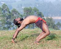 Indian man doing yoga exercises on green grass. Healthy life exercise concept - athletic Indian man doing backbend yoga exercises on green grass in Kerala, South Stock Photo