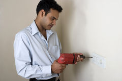 Indian man drilling hole in a wall Royalty Free Stock Photography
