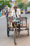 Indian man driving bicycle rickshaw at crowded city street Royalty Free Stock Image