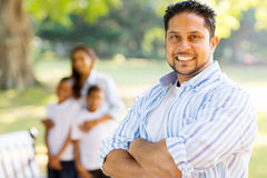 Indian man family. Good looking young indian man standing in front of family outdoors Royalty Free Stock Image