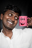 Indian man with funny mug. Handsome Indian man with funny mug smiling and looking at it close-up royalty free stock image