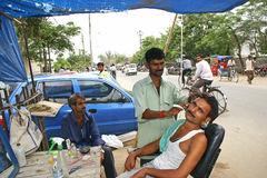 Indian man getting his shave from the roadside shop. Stock Image