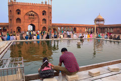Indian man with a girl sitting at the pool in Jama Masjid in Del Stock Photos