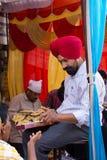 Indian man giving away rice at Guru Nanak Gurpurab celebration, Stock Images