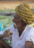 Indian man with green turban smoking a cigarett Stock Image