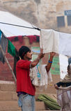 Indian man hang the wash on clothesline on ghat near sacred river Ganges in Varanasi Royalty Free Stock Photo