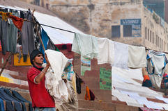 Indian man hang the wash on clothesline on ghat near sacred river Ganges in Varanasi Royalty Free Stock Photography