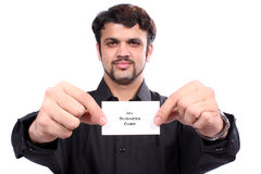 Indian Man Holding Business Card. A proud Indian man showing his new business card, on white studio background. Focus on hands and the card Stock Images