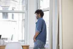 Indian man at home looking out of the window. Stock Photos