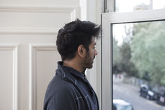 Indian man at home looking out of the window. Royalty Free Stock Photos