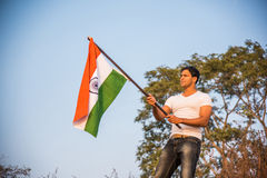 Indian man and indian flag. Young and handsome indian man holding and waving indian national flag or tricolour at outdoor location near lake royalty free stock photo