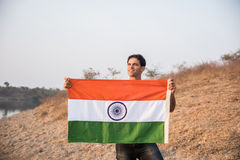 Indian man and indian flag. Young and handsome indian man holding and waving indian national flag or tricolour at outdoor location near lake royalty free stock photography
