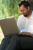 Indian man with a laptop. Indian man sitting in the forest with a laptop Royalty Free Stock Images