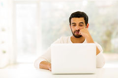 Indian man laptop. Focused indian man looking at laptop screen Royalty Free Stock Photography