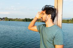 Indian man looking far away near lake stock photography
