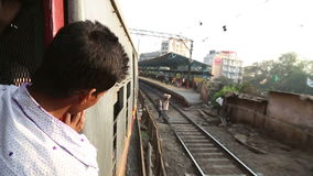 Indian man looking out of the window during train ride. MUMBAI, INDIA - 12 JANUARY 2015: Indian man looking out of the window during train ride stock video footage