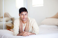 Indian man lying on bed Stock Photography