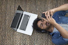 Indian man lying on the floor at home with laptop and phone. Royalty Free Stock Photos