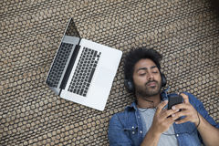 Indian man lying on the floor at home with laptop and phone. Royalty Free Stock Photography